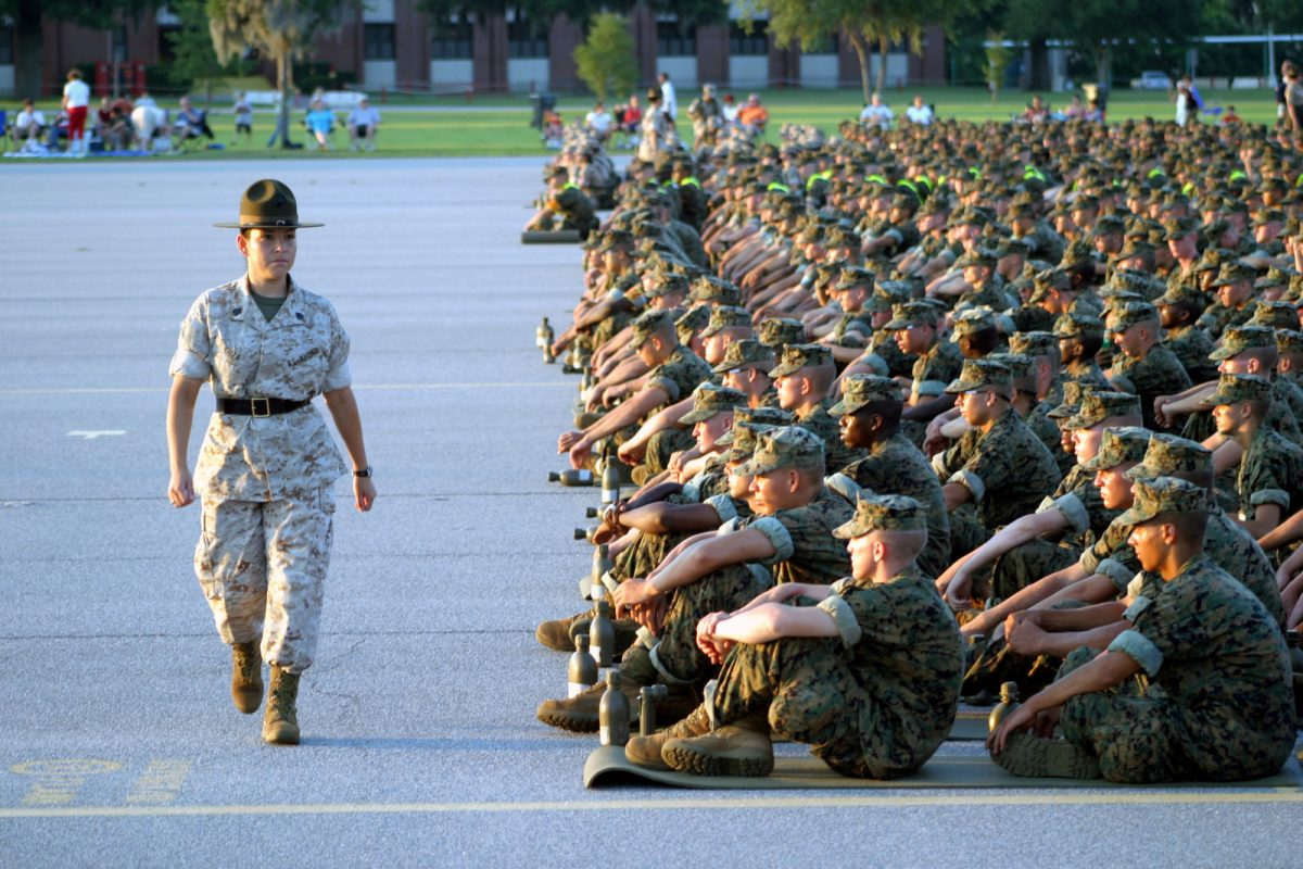 A US Marine Corps female Drill Instructor inspects the discipline of the recruits who are seated and lined up in platoon order during the annual Independence Day celebration at Parris Island. (Credit: U.S. National Archives)